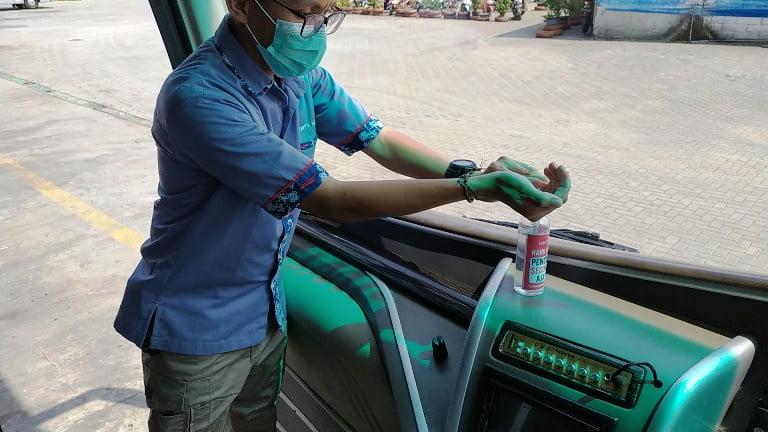 001 Karyawan WEHA menggunakan hand sanitizer di dalam bus