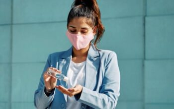 woman with medical mask airport using hand sanitizer during pandemic 23 2148789877